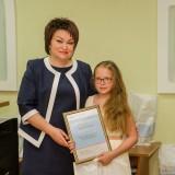 Директор по социальным вопросам ОЭМК Ирина Дружинина вручает благодарность Кире Липченко